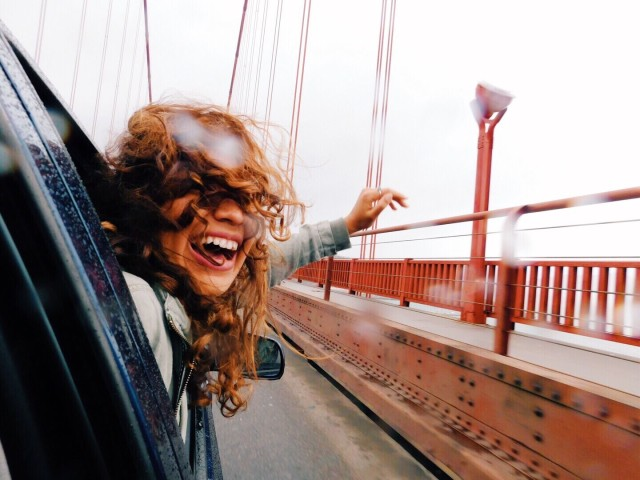 stock-photo-bridge-rain-fun-driving-windblown-car-ride-happy-girl-windy-hair-a2e68ab0-538e-40a5-bd76-9aa71ea3b1d3